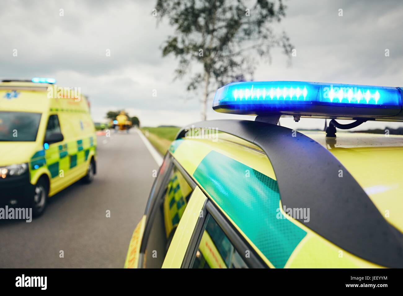 Ambulance cars. Teams of the Emergency medical service are responding to an traffic accident in bad weather. - Stock Image