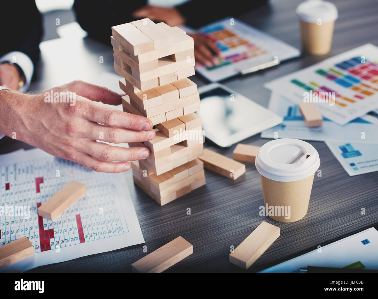 Teamwork of partners. Concept of integration and startup with a small construction of wooden toy - Stock Image