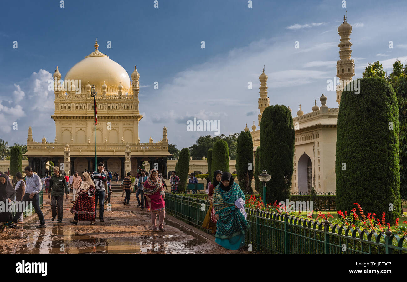 Mysore, India - October 26, 2013: Cream yellow Tipu Sultan mausoleum with dome and mosque under heavy cloudscape. - Stock Image