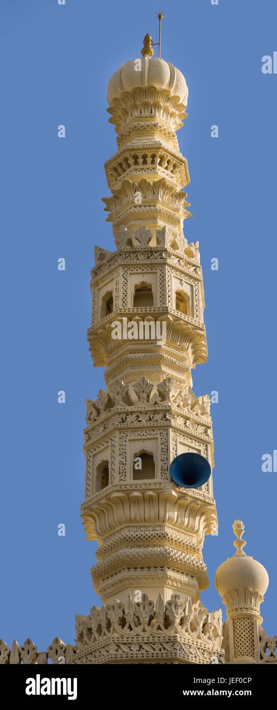 Mysore, India - October 26, 2013:Closeup of cream yellow minaret of mosque at Tipu Sultan mausoleum under deep blue - Stock Image