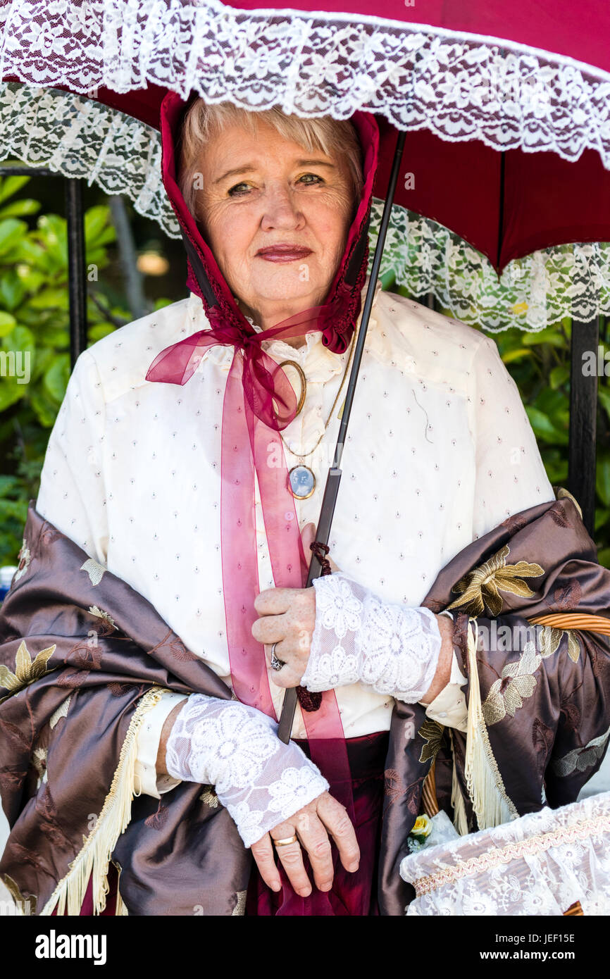 Portrait, outdoors, facing, senior woman, 60s, dressed up in Victorian costume. Shawl around shoulders, red hat - Stock Image