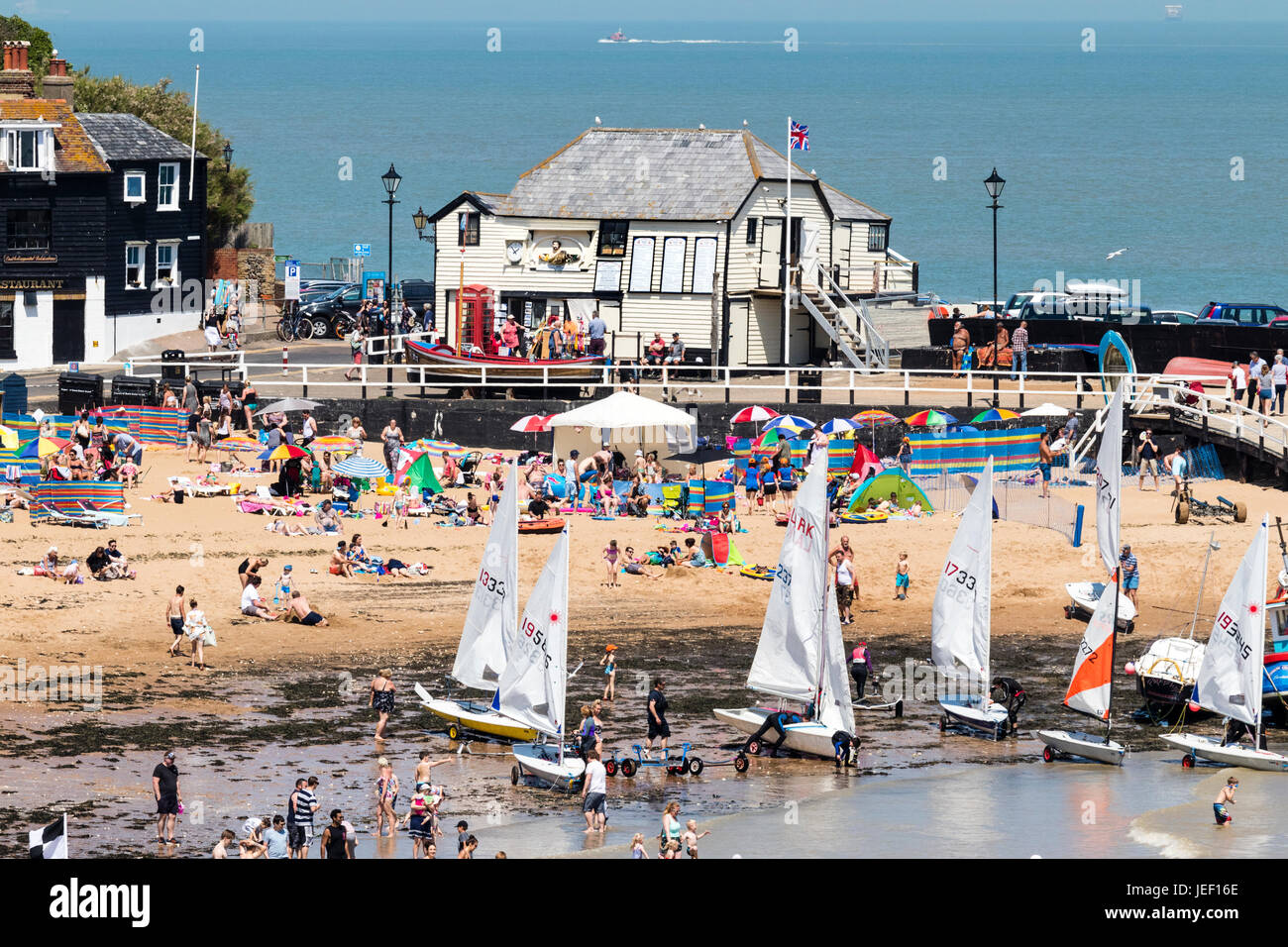 Broadstairs famous former life boat station, wooden white building on the harbour jetty. Foreground, crowds on the - Stock Image