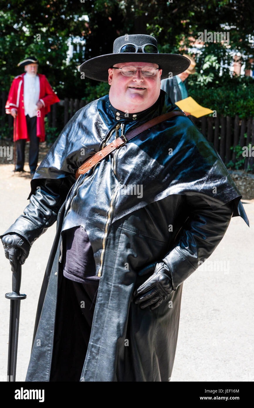 Steampunk, large Caucasian man, 40s, in black leather coat and wide brimmed hat with goggles. Smiling. - Stock Image