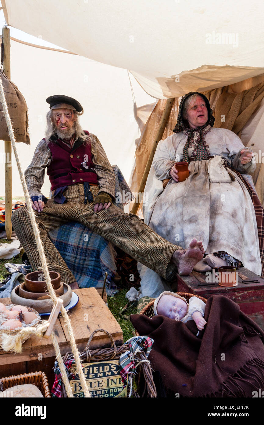 Navy, and his wife, 'Voices From Victorian London' Living History players, relaxing in their home (tent). - Stock Image
