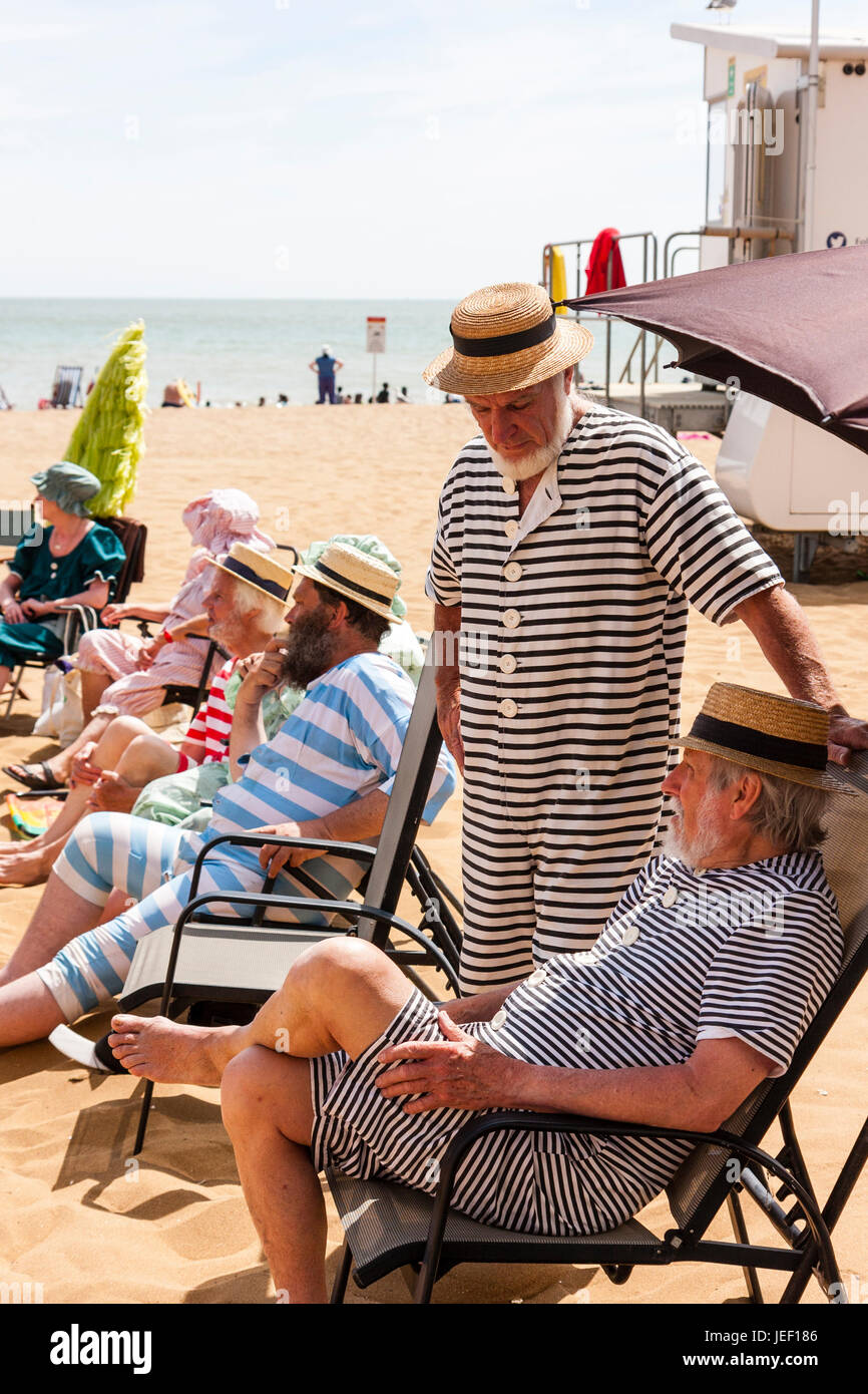 Dickensian style beach party, Row of men sitting, with one standing, in deckchairs all wearing straw hats and Victorian - Stock Image