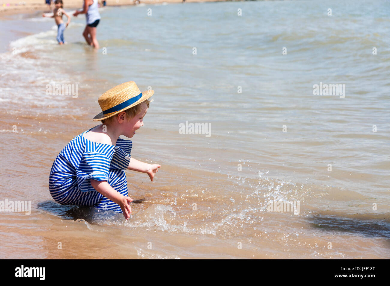 Caucasian blonde child, boy, 4-5 years old, kneeling in the surf on a beach, wearing straw hat and blue and white - Stock Image