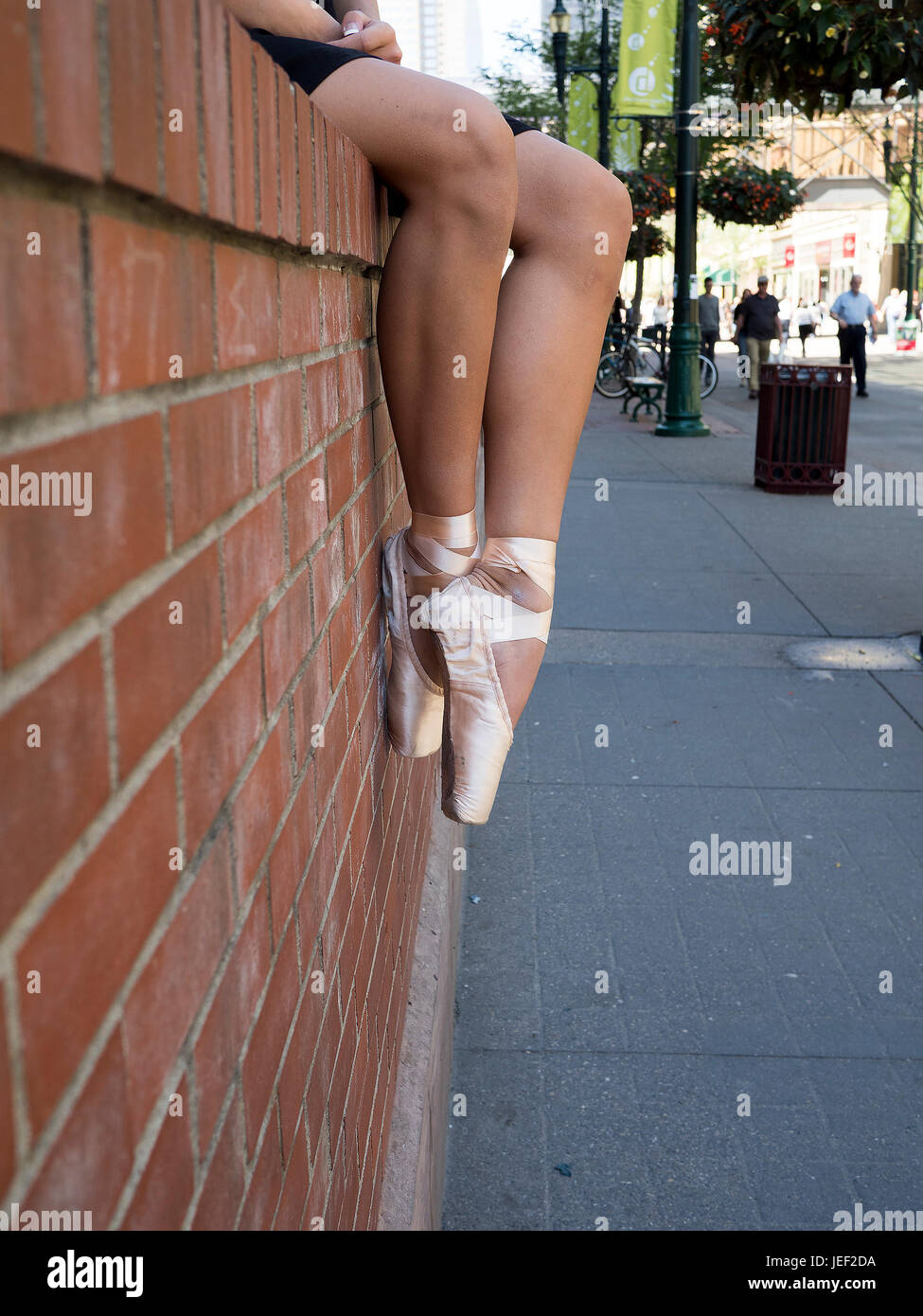Legs and Feet of a Ballet dancer in Pointe Shoes In an Urban Area - Stock Image