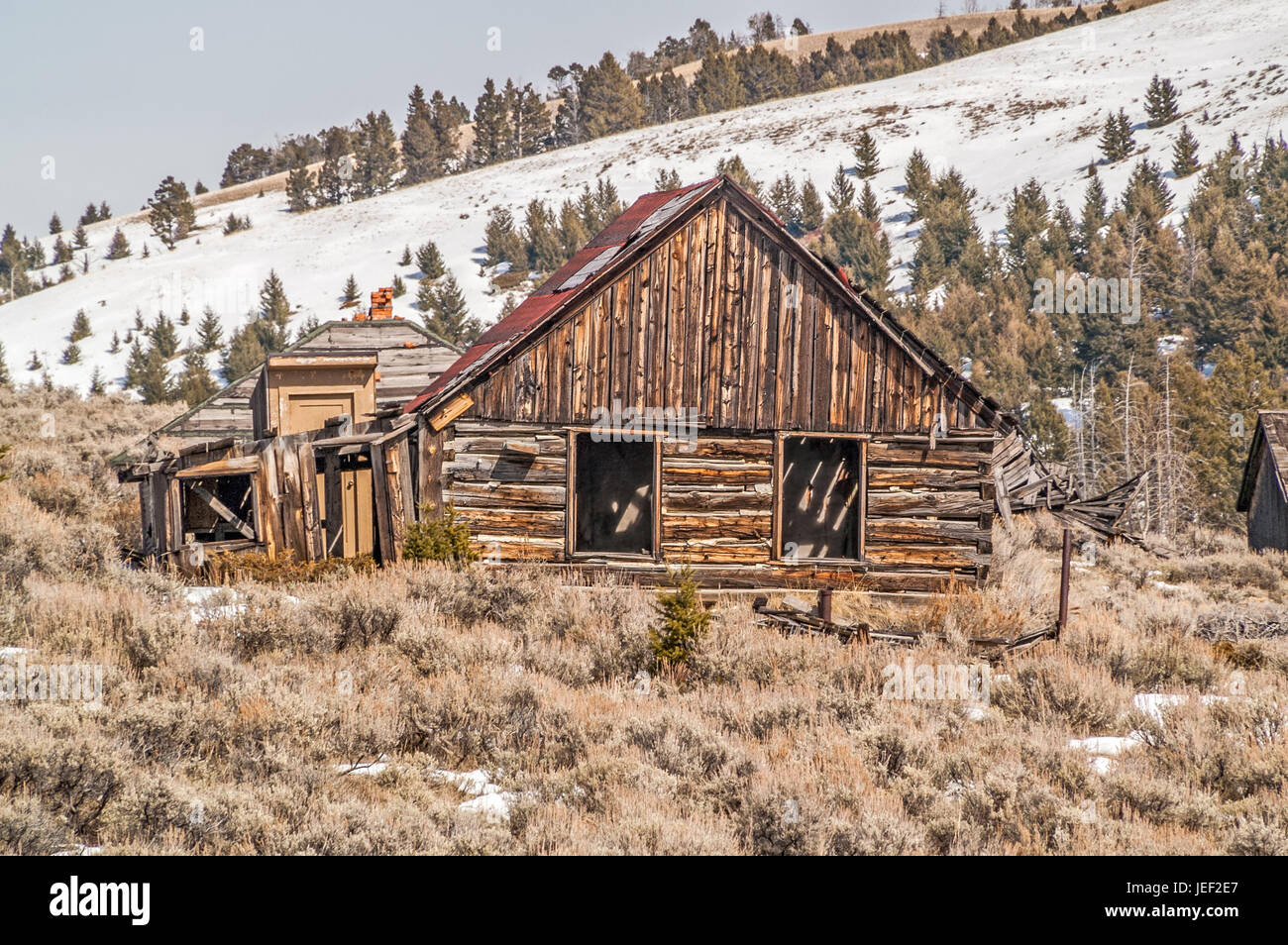 Log schoolhouse in a ghost town with nearby homes in various stages of neglect - Stock Image