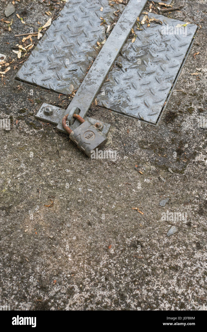 Locked padlock blocking access to manhole cover. Possible metaphot for data security and IT security. Protect your Stock Photo