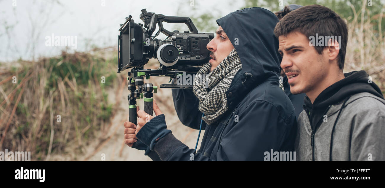 Behind the scene. Cameraman and film director shooting film scene on outdoor location - Stock Image
