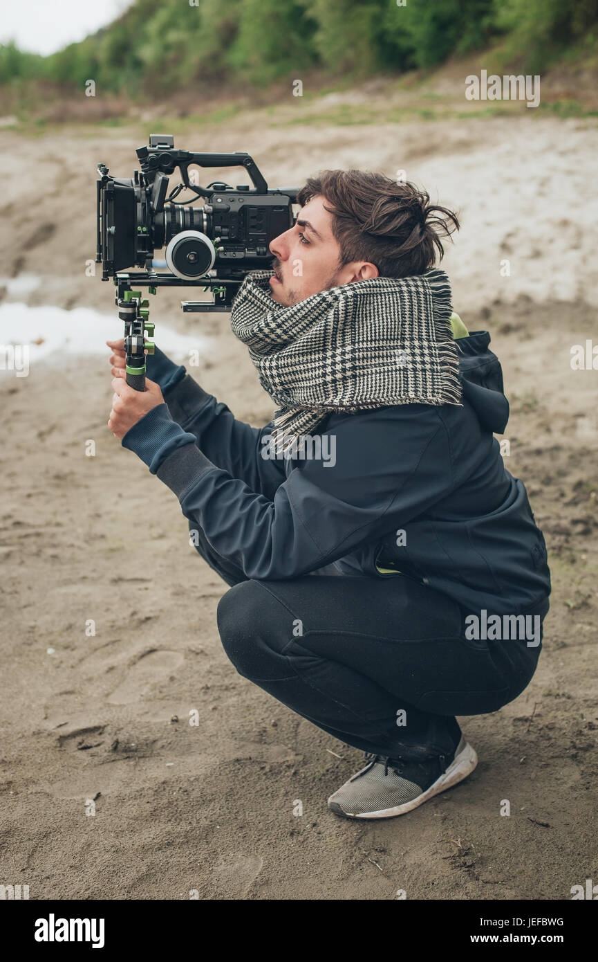 Behind the scene. Cameraman shooting the film scene with his camera on outdoor location - Stock Image