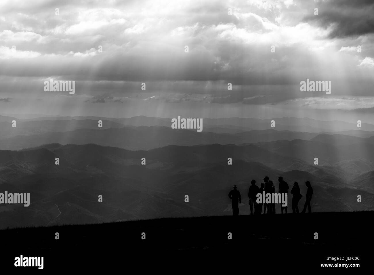 Some people on top of a mountain, with other mountains and hills in the background, and sunrays coming out of the - Stock Image