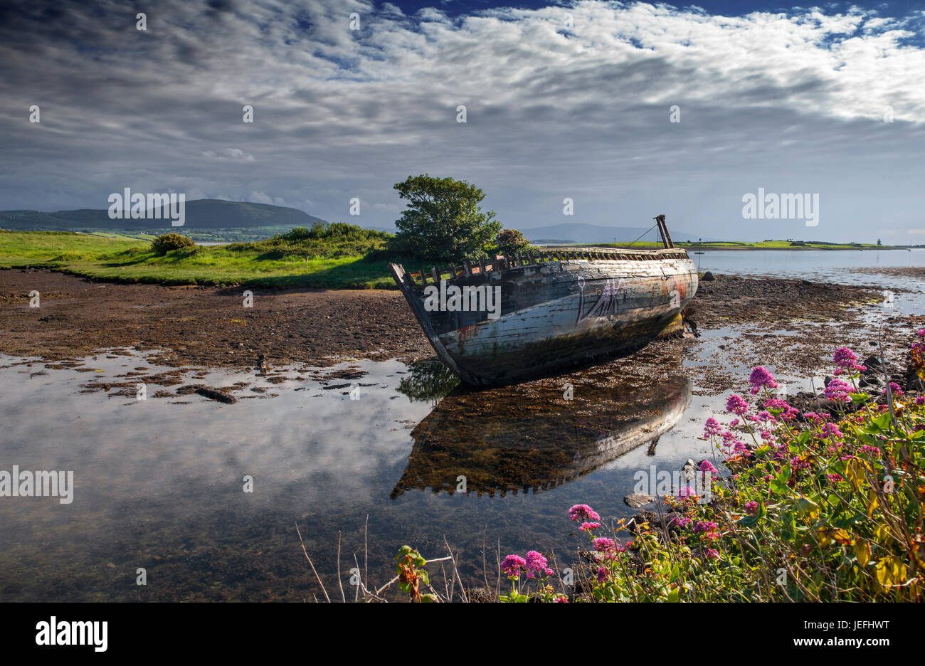 An old wrecked fishing boat on the Garavogue River at Rosses Point, County Sligo, Ireland - Stock Image