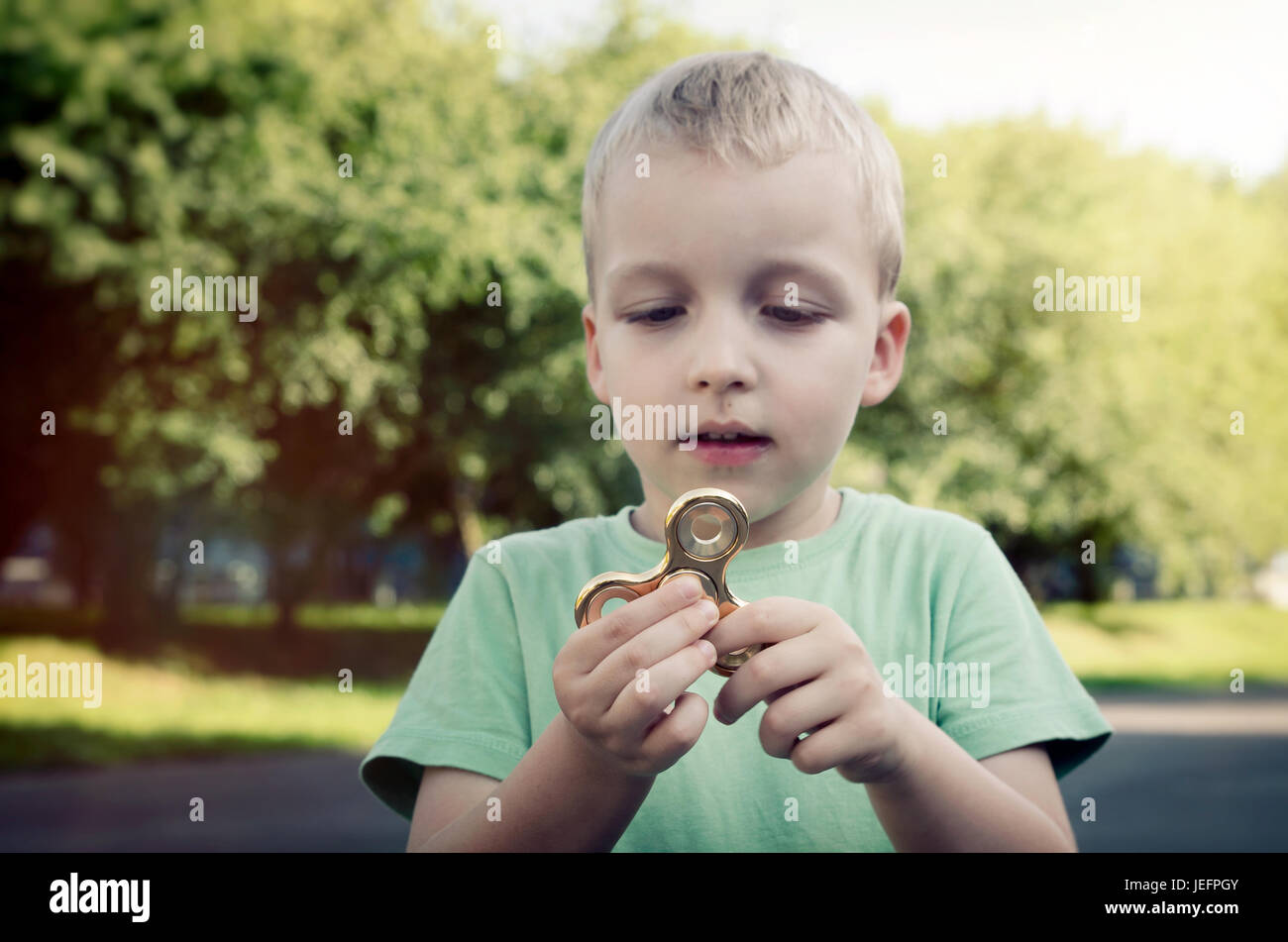 Little boy with a fidget spinner outdoors. spinner fidget child stress adhd attention fad boy concept - Stock Image