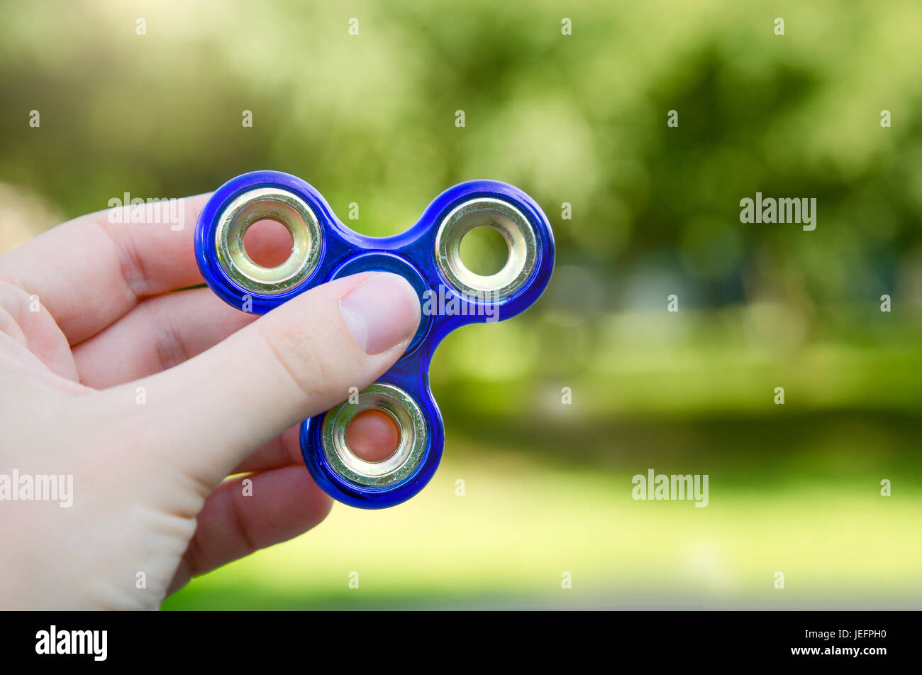 Fidget spinner in hand close up. spinner fidget child stress adhd attention fad boy concept - Stock Image