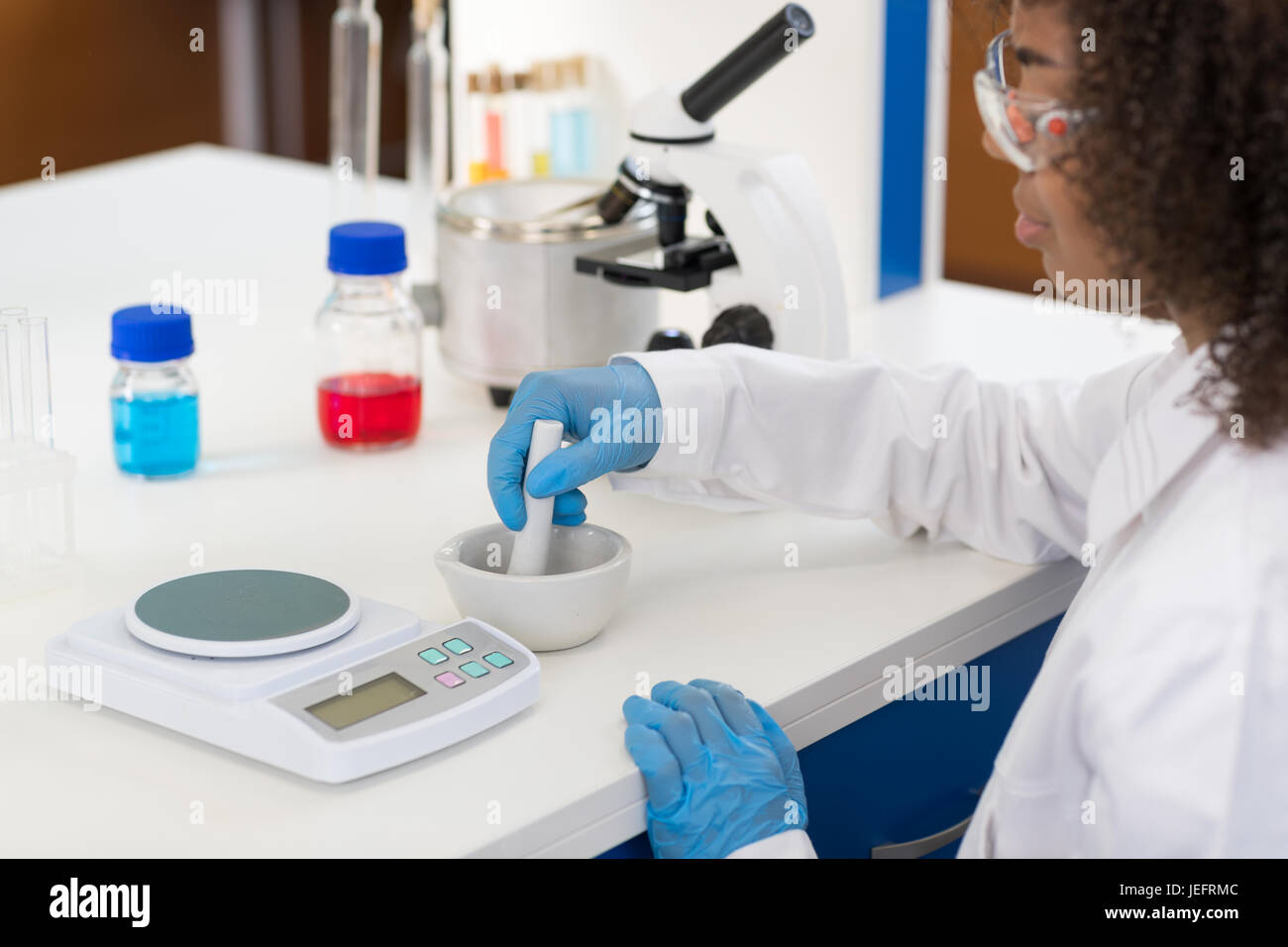 Female Scientist Using Mortar Working In Laboratory Making Chemicals Powder For Experiment, Researcher Mix Race - Stock Image