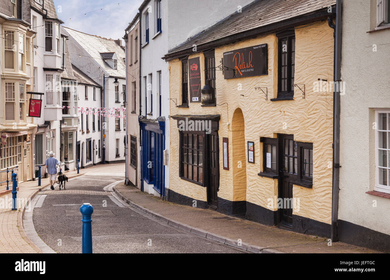 14 June 2017: Ilfracombe, North Devon, England, UK - A man walks with his greyhound down Fore Street, formerly the - Stock Image