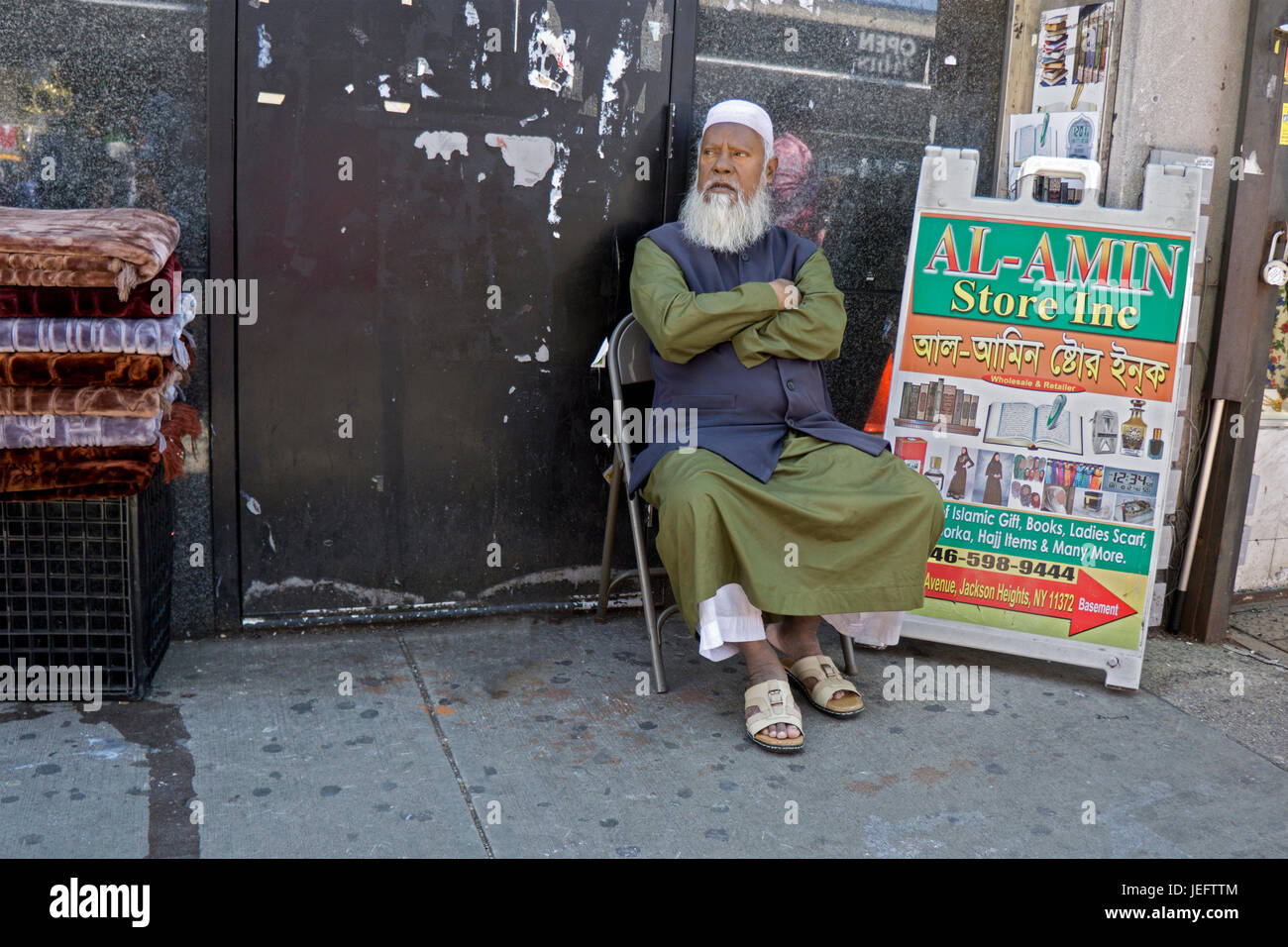 An older Islamic merchant rests while watching his stand on 37th Avenue in Jackson Heights, Queens, New York Stock Photo