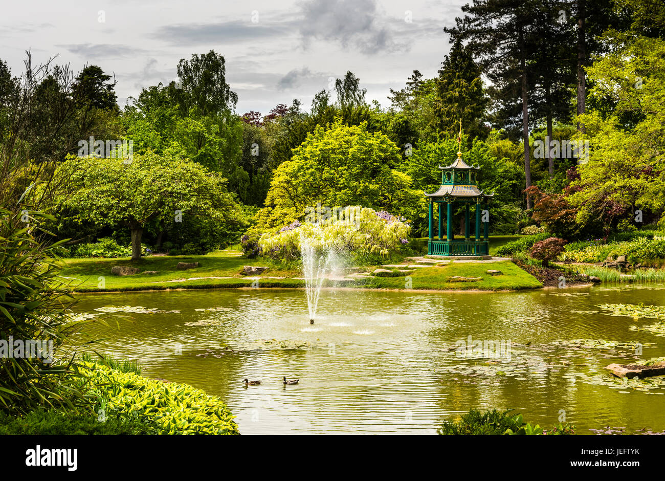 Lake, fountain and pergola in the water gardens at Cliveden, Buckinghamshire, UK - Stock Image