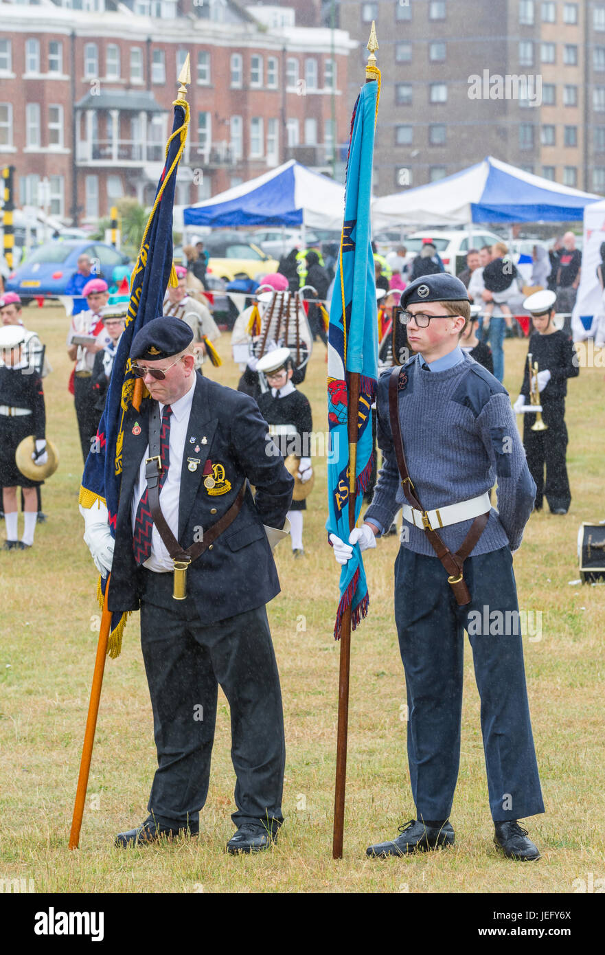 Young and old military men standing at an outdoor service on the June 2017 Armed Forces day in Littlehampton, UK. - Stock Image