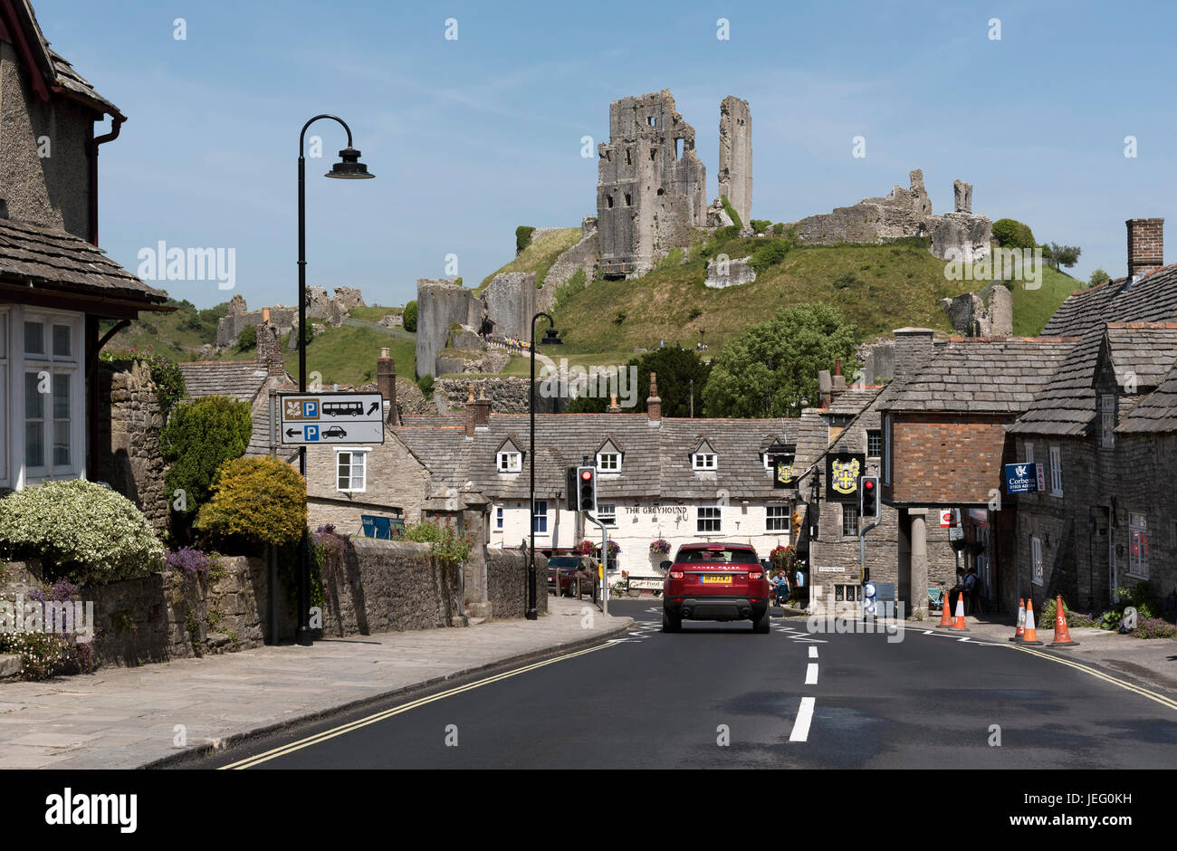 The main road through Corfe Castle a historic Dorset town with a ruined castle on the hill. June 2017 - Stock Image