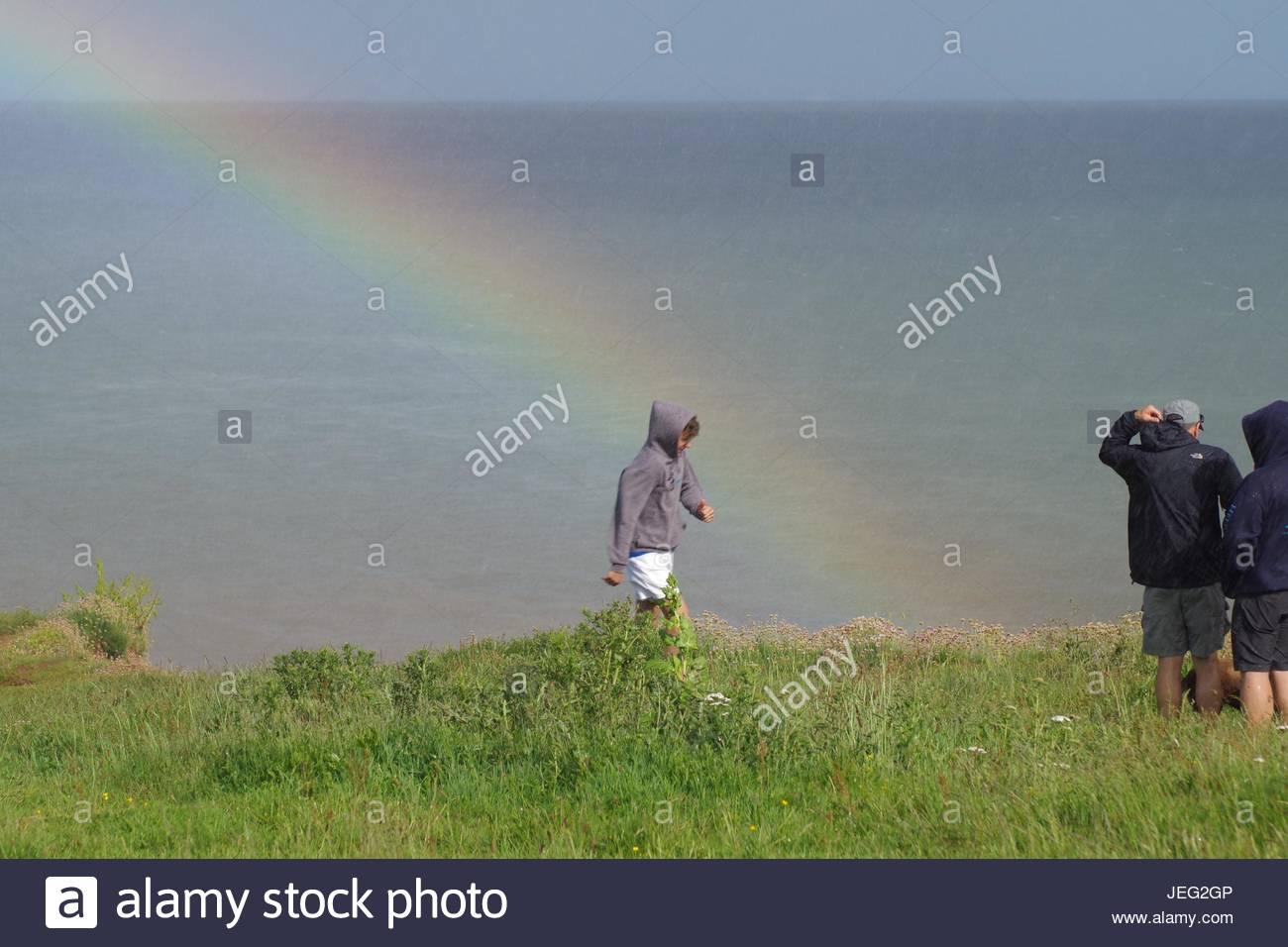Family Atop Langstone Rock Under a Rainbow on a Rainy Summer Day, Dawlish, Devon, UK. - Stock Image