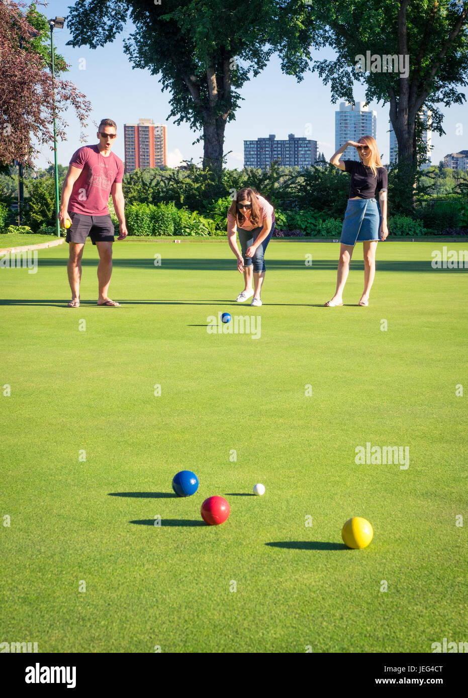 Friends play bocce ball on a manicured bowling green at the Royal Lawn Bowling Club in Edmonton, Alberta, Canada. - Stock Image