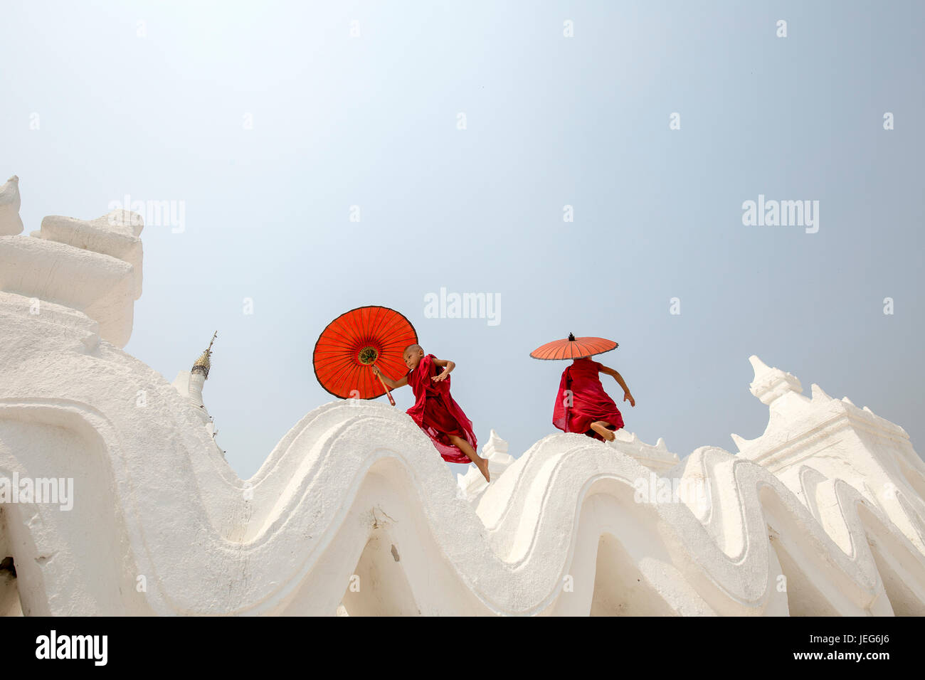Monks with umbrella in Hsinbyume Pagoda Temple in Mandalay Myanmar Mingon Sagaing region White temple pagoda Myanmar - Stock Image