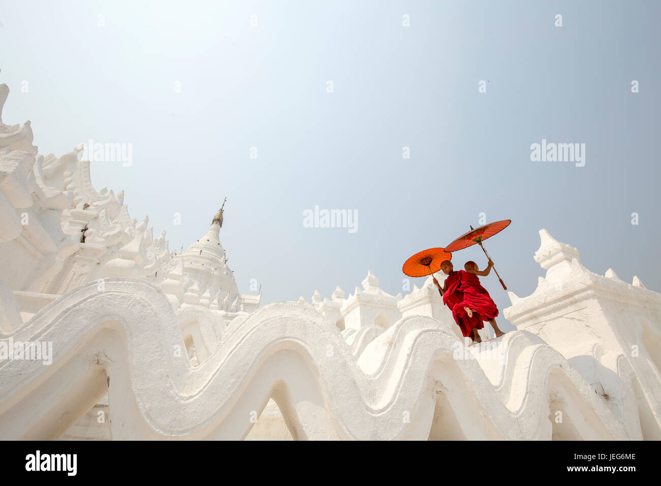 Monks with umbrella in Hsinbyume Pagoda Temple in Mandalay Myanmar Mingon Sagaing region White temple pagoda Myanmar Stock Photo