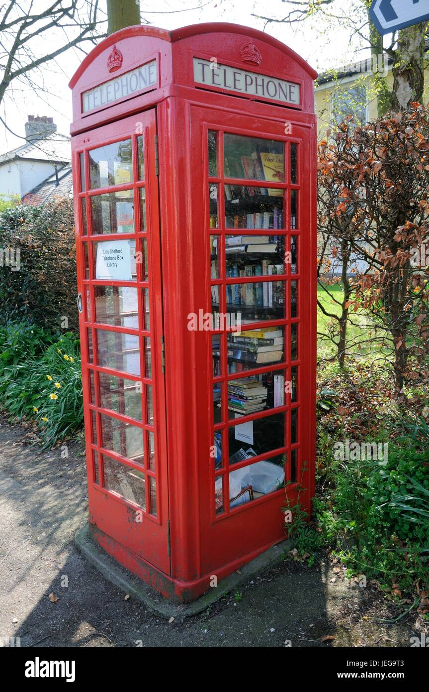 Telephone Kiosk Library, High Street, Little Shelford, Cambridgeshire. It was purchased by the parish council and - Stock Image