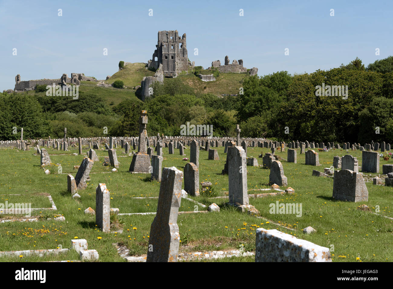 Ruined castle overlooks the cemetery at Corfe Castle Dorset England UK. June 2017 - Stock Image