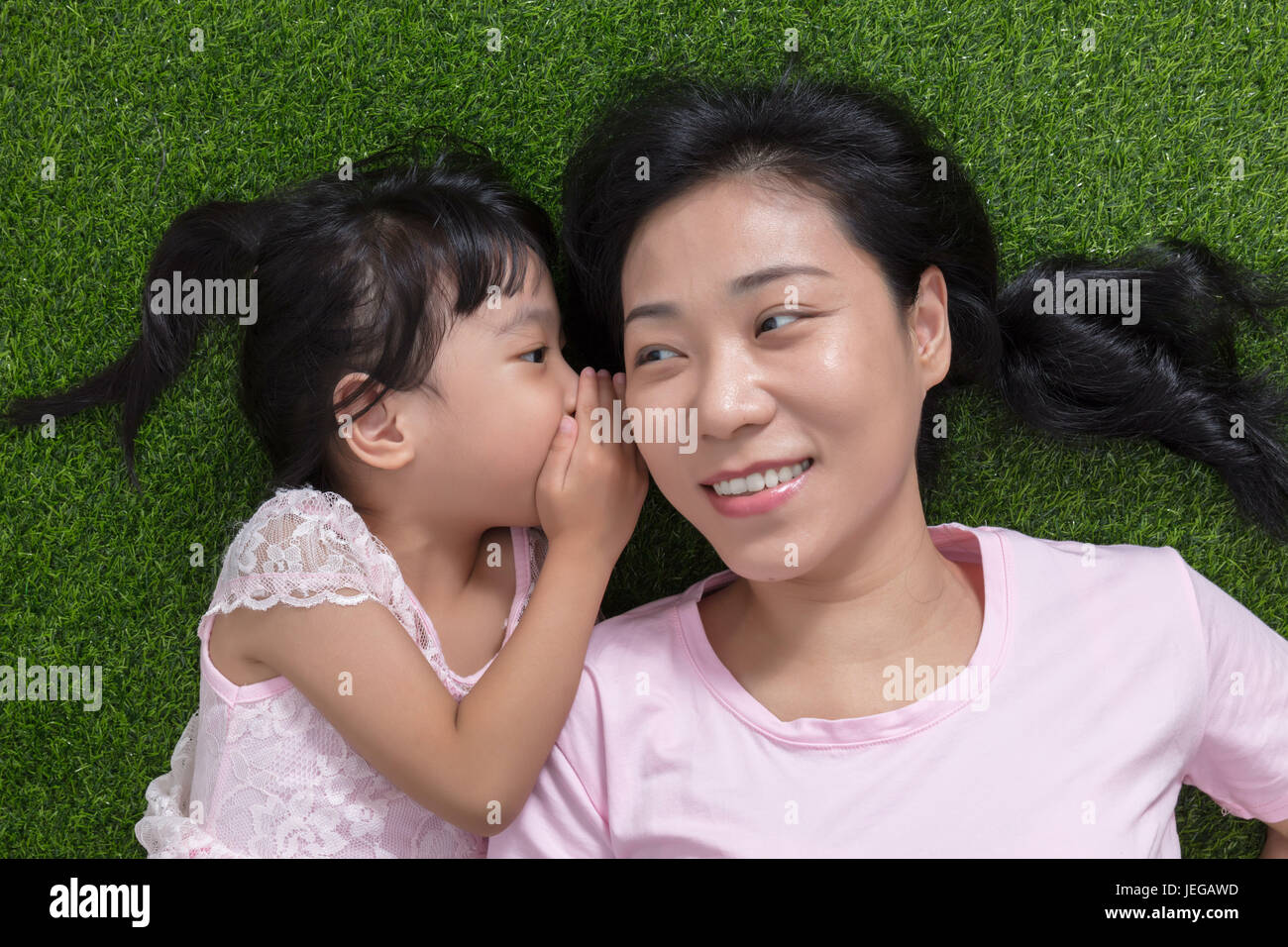 Asian Chinese mother and daughter lying on the grass whispering and gossiping at outdoor park - Stock Image