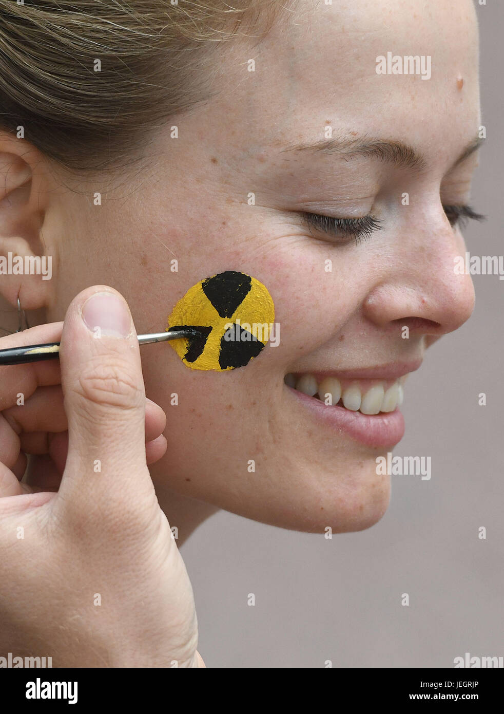 Aachen, Germany. 25th June, 2017. A participant in the protest has her cheek painted with a radiation symbol during - Stock Image
