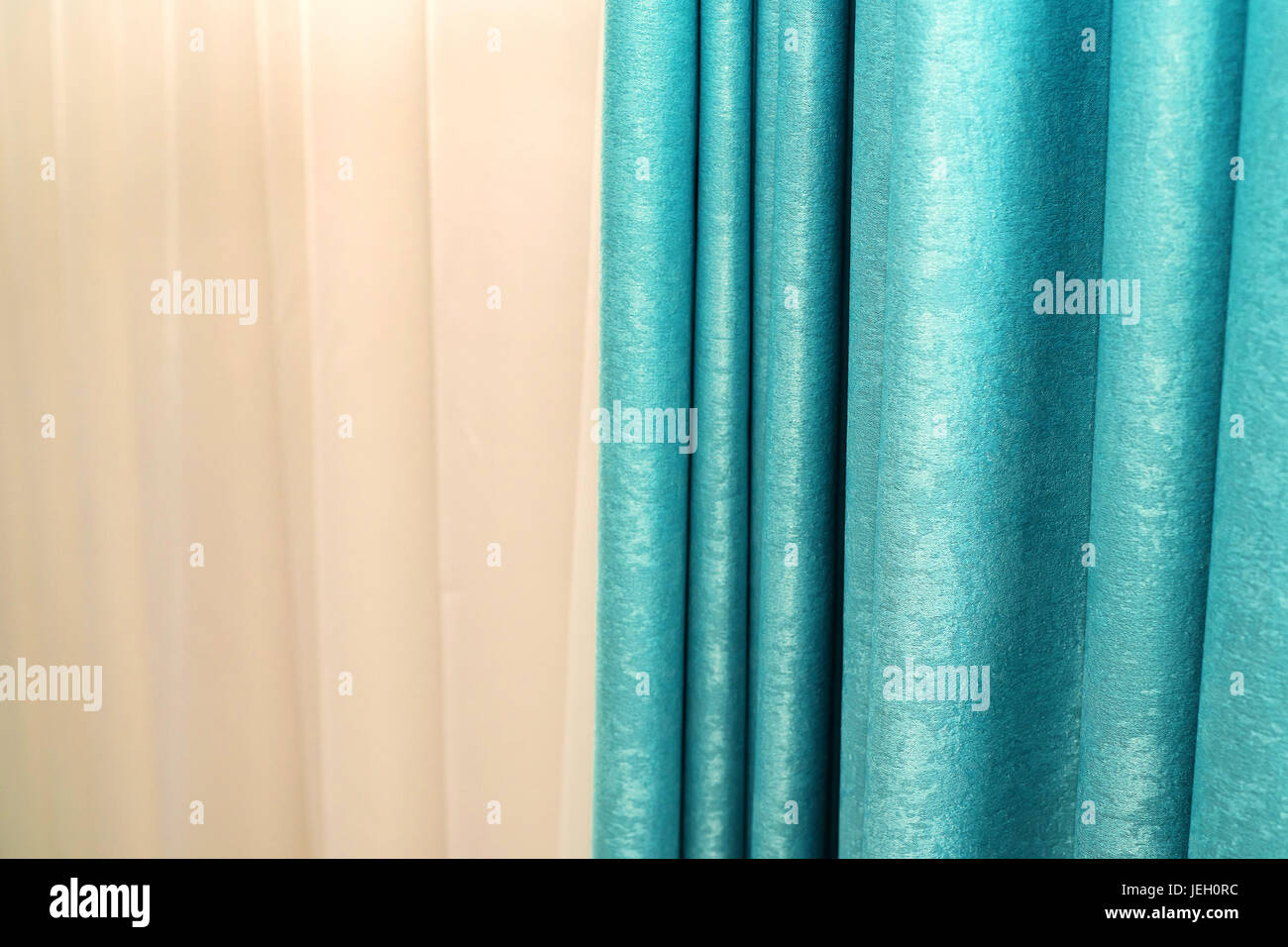Bright blue curtain with beige wall in background Stock Photo