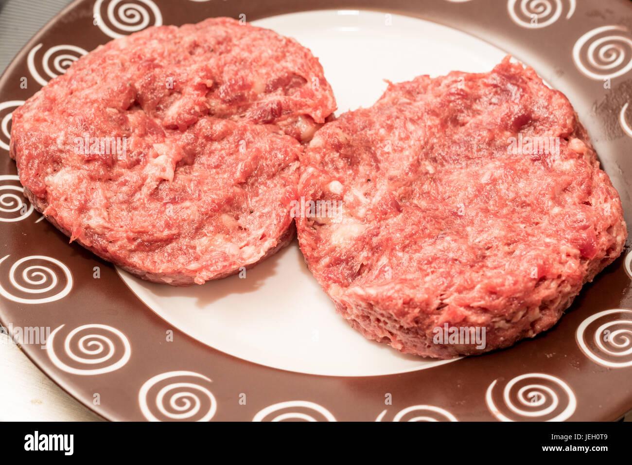 Fresh raw beef burger patties on plate - Stock Image