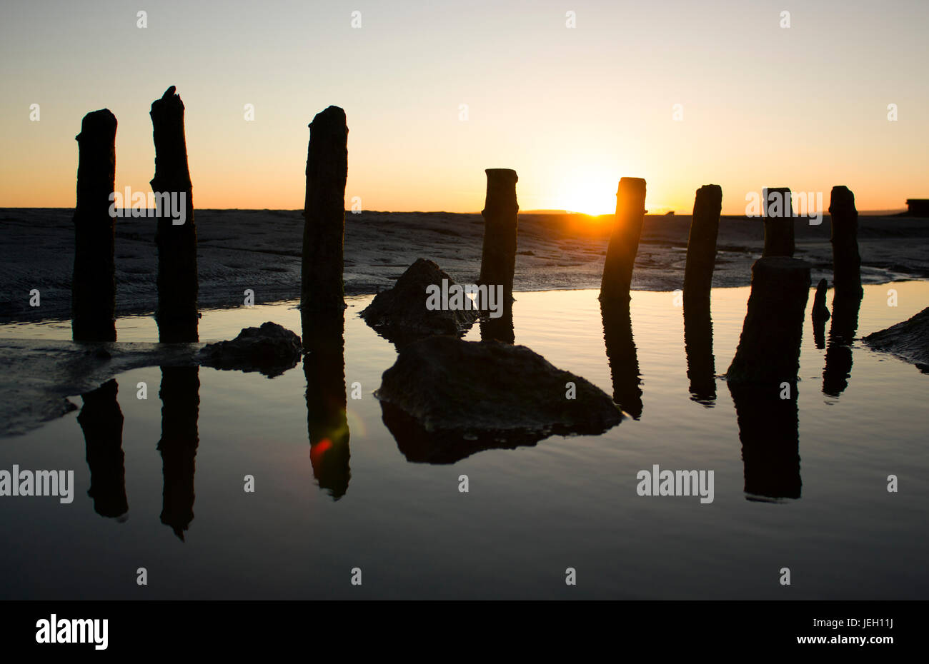 Grange-over-Sands beach sunset, near the Lake District. The low sun creating shadows. wooden stakes may have been Stock Photo