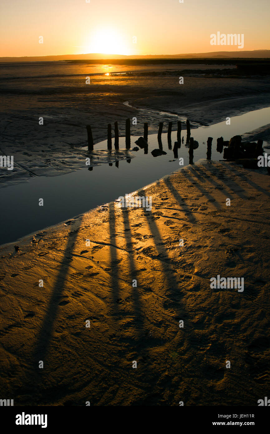 Grange-over-Sands beach sunset, near the Lake District. The low sun creating shadows. wooden stakes may have been - Stock Image