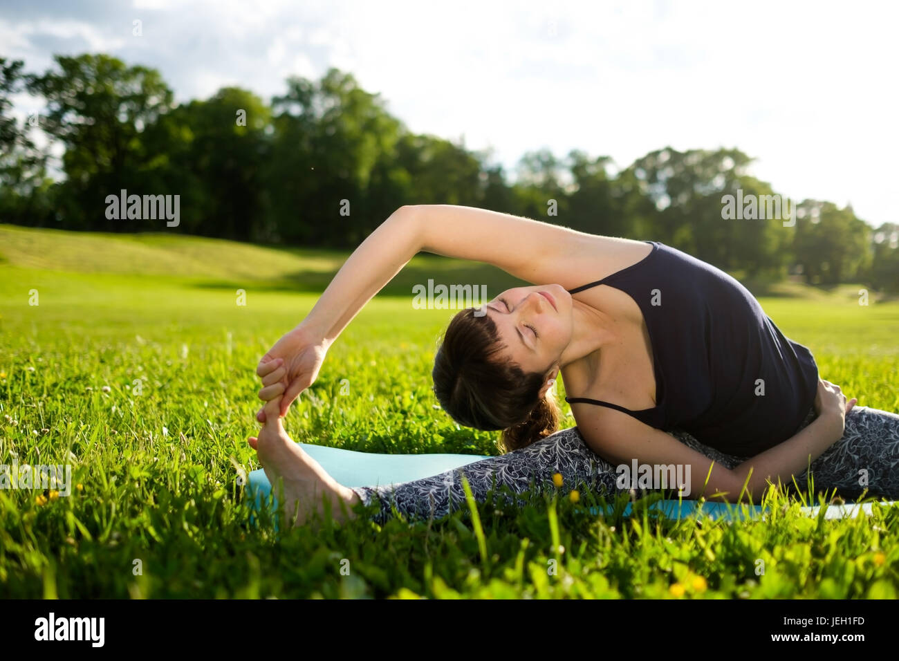 Woman practices yoga asana in park in the morning. - Stock Image