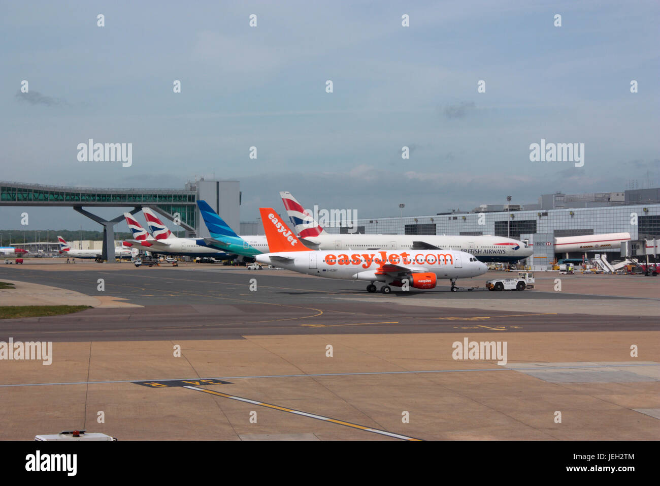 Civil aviation. London Gatwick Airport, UK, with planes at their gates and an easyJet Airbus A319 in the foreground - Stock Image