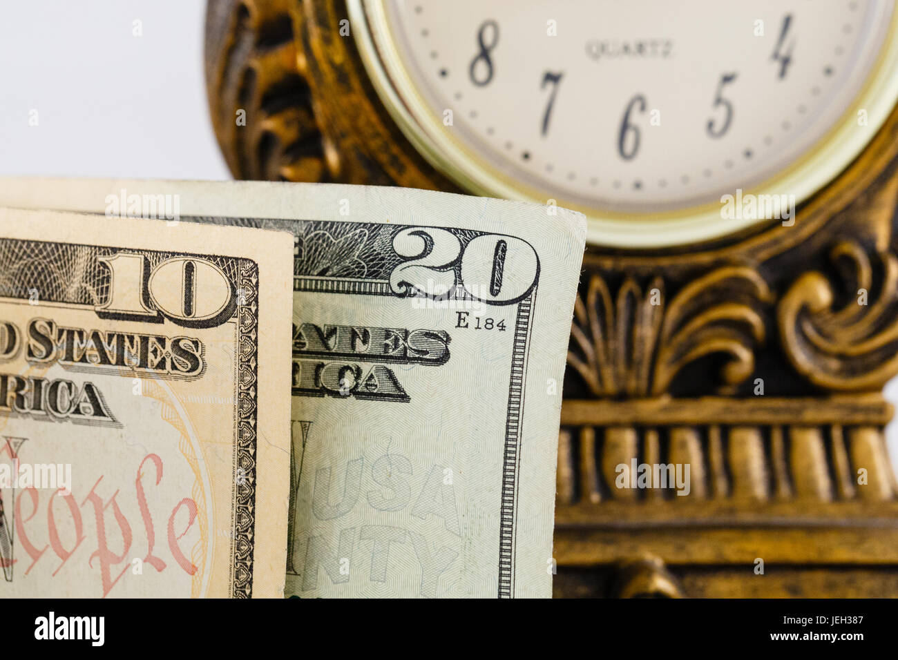 Close up of american cash money with a clock in the background - Stock Image