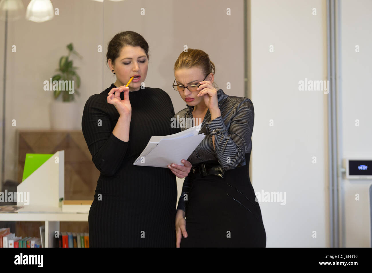 Two business women at work in different regular office situations. - Stock Image