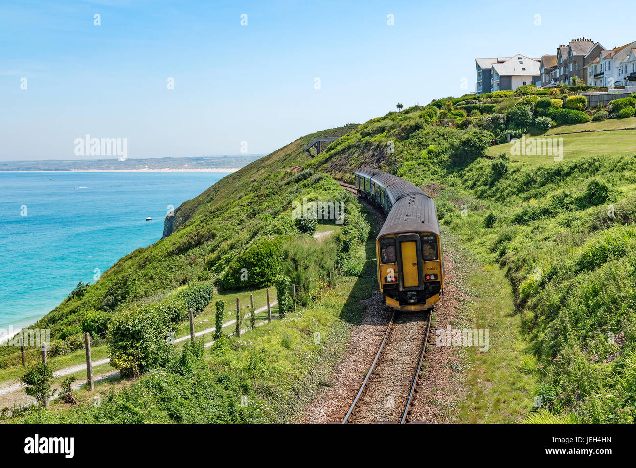 the st.ives branch railway line passing carbis bay in cornwall, england, britain, uk. - Stock Image
