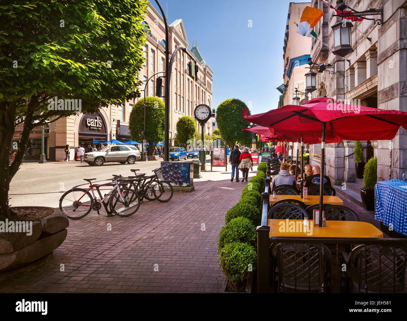 People on a terrace of Irish Times Pub restaurant, Government street in downtown Victoria, BC on a sunny summer - Stock Image
