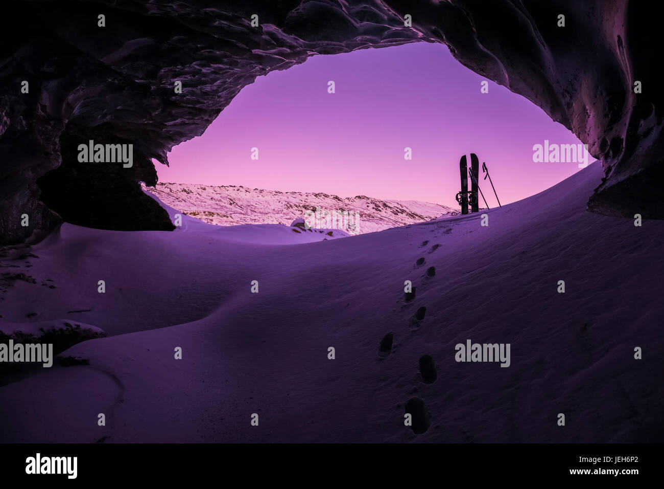 Footprints lead toward a splitboard placed at the entrance of an ice cave within Canwell Glacier in the Alaska Range - Stock Image