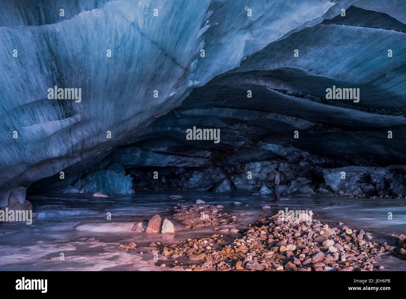 A man stands inside a cavernous ice cave at the terminus of Augustana Glacier in the Alaska Range in winter; Alaska, - Stock Image