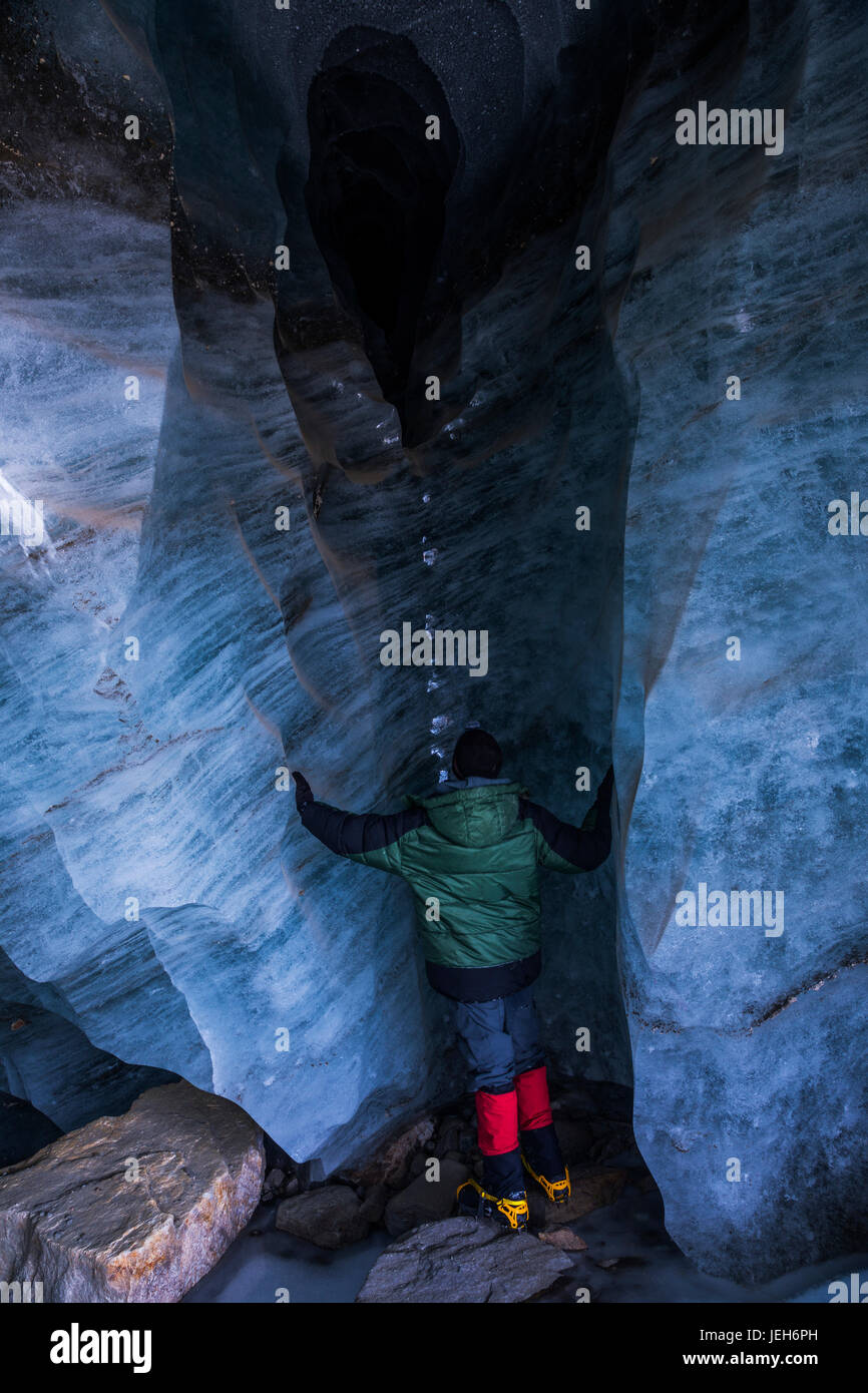 A man stands beneath an opening in the ice of Augustana Glacier where water empties from the glacier's drainage - Stock Image