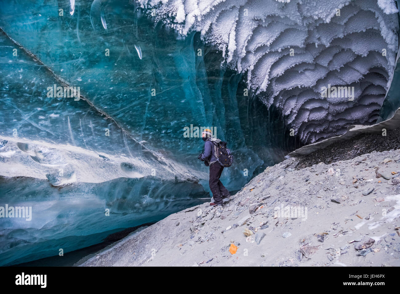 A man explores a tunnel beneath the ice of Canwell Glacier in the Alaska Range in winter; Alaska, United States - Stock Image