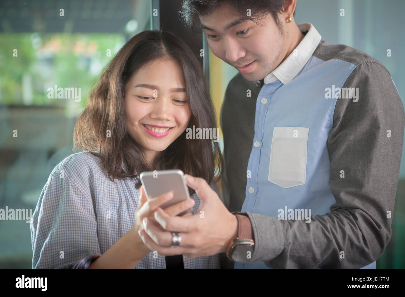 asian younger man and woman looking to smart phone screen toothy smiling face happiness emotion - Stock Image
