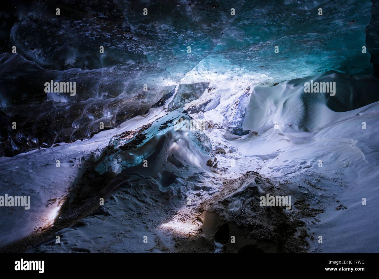 Strange light shines on the floor of a cave beneath the ice of Castner Glacier in the Alaska Range; Alaska, United - Stock Image