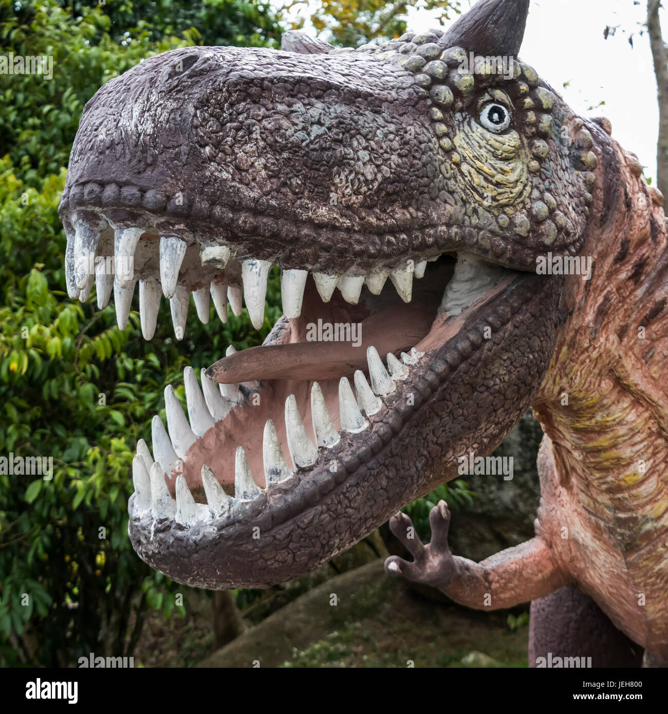 Sculpture of a dinosaur with a wide open mouth showing it's